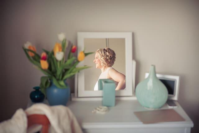 Bride putting on wedding dress mirror reflection photograph