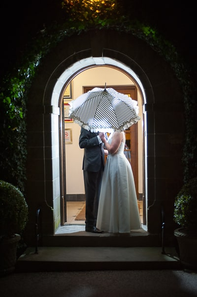 Bride and groom with silhouette behind umbrella