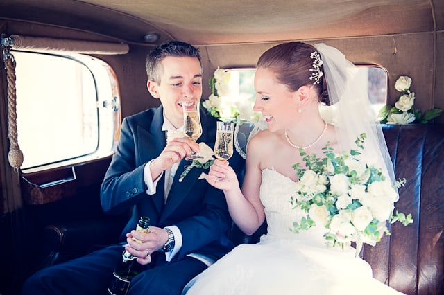 wedding photograph of Bride and groom with champagne in Rolls Royce wedding car
