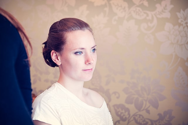 portrait of bride on wedding morning with patterned wallpaper