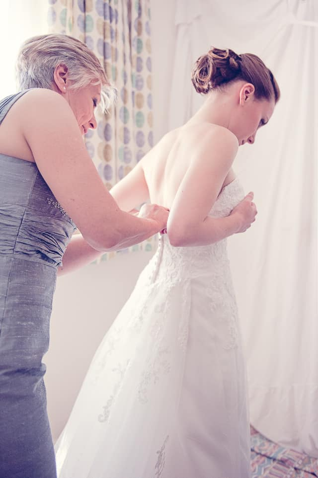 mother of bride helps with on wedding dress