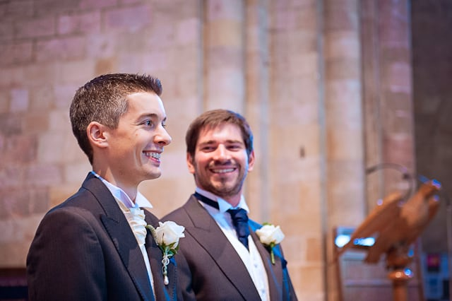 Groom and best man share a joke at Romsey Abbey