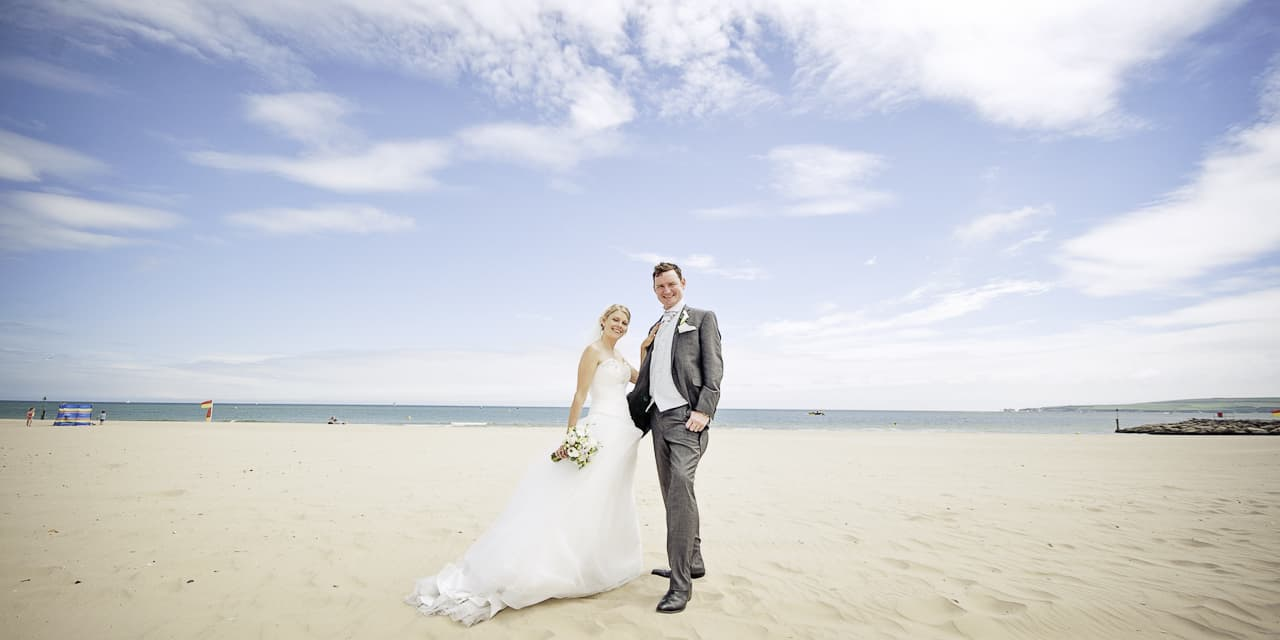 Bride and groom on Sandbanks beach with blue skies and sea in Dorset