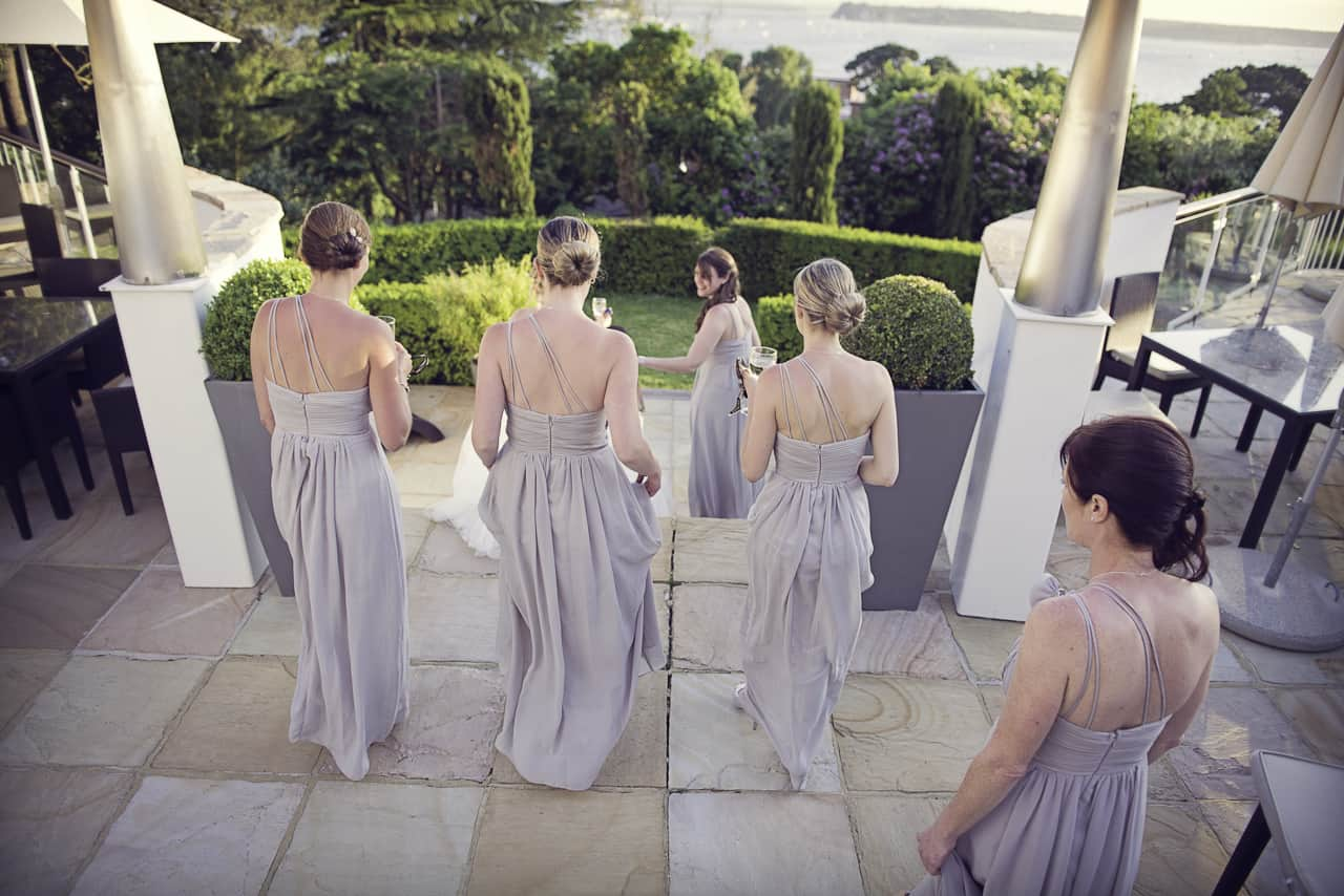Bridesmaids in silver dresses at Harbour Heights Hotel gardens Dorset Wedding