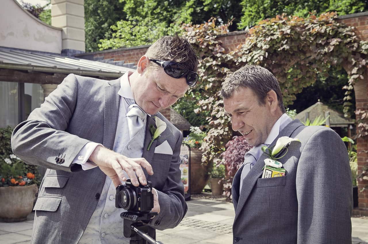 Groom and grooms man in grey suits set up the wedding videography