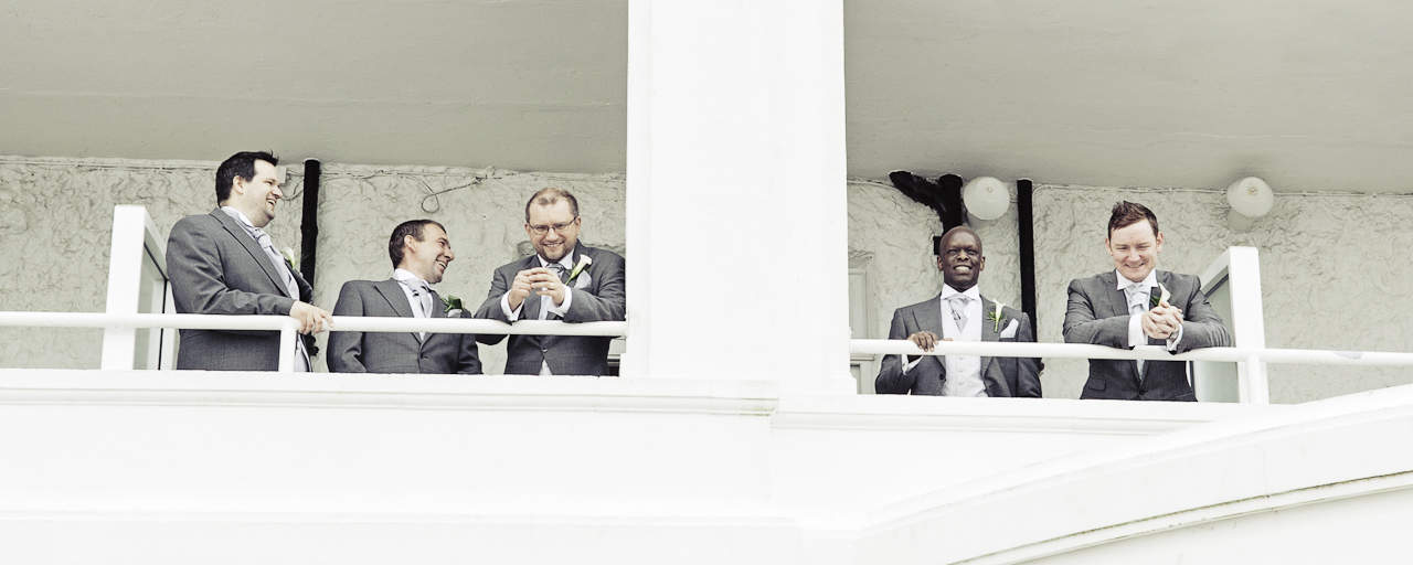Groomsmen in grey suits on Haven Hotel balcony on wedding morning