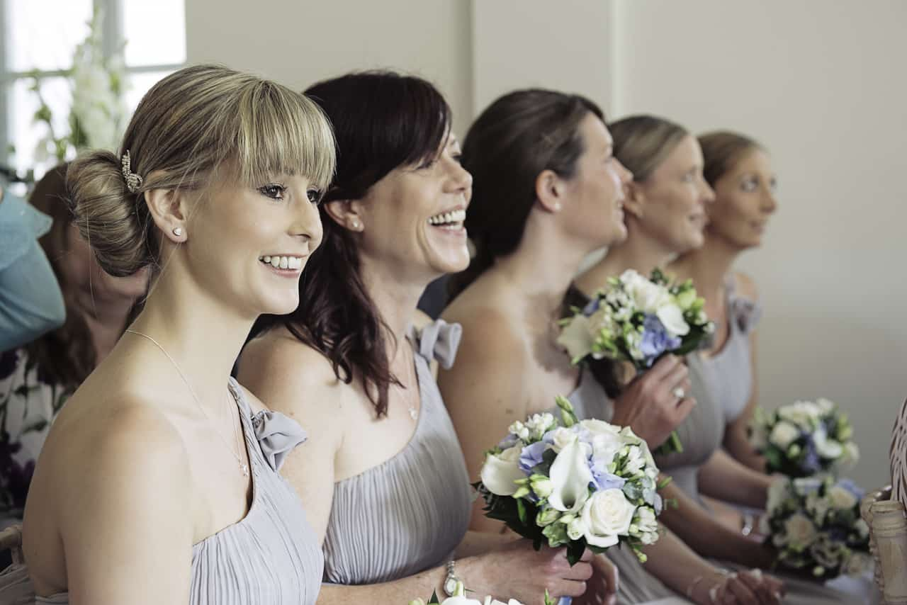 Happy bridesmaids in silver dresses holding white and blue wedding bouquets