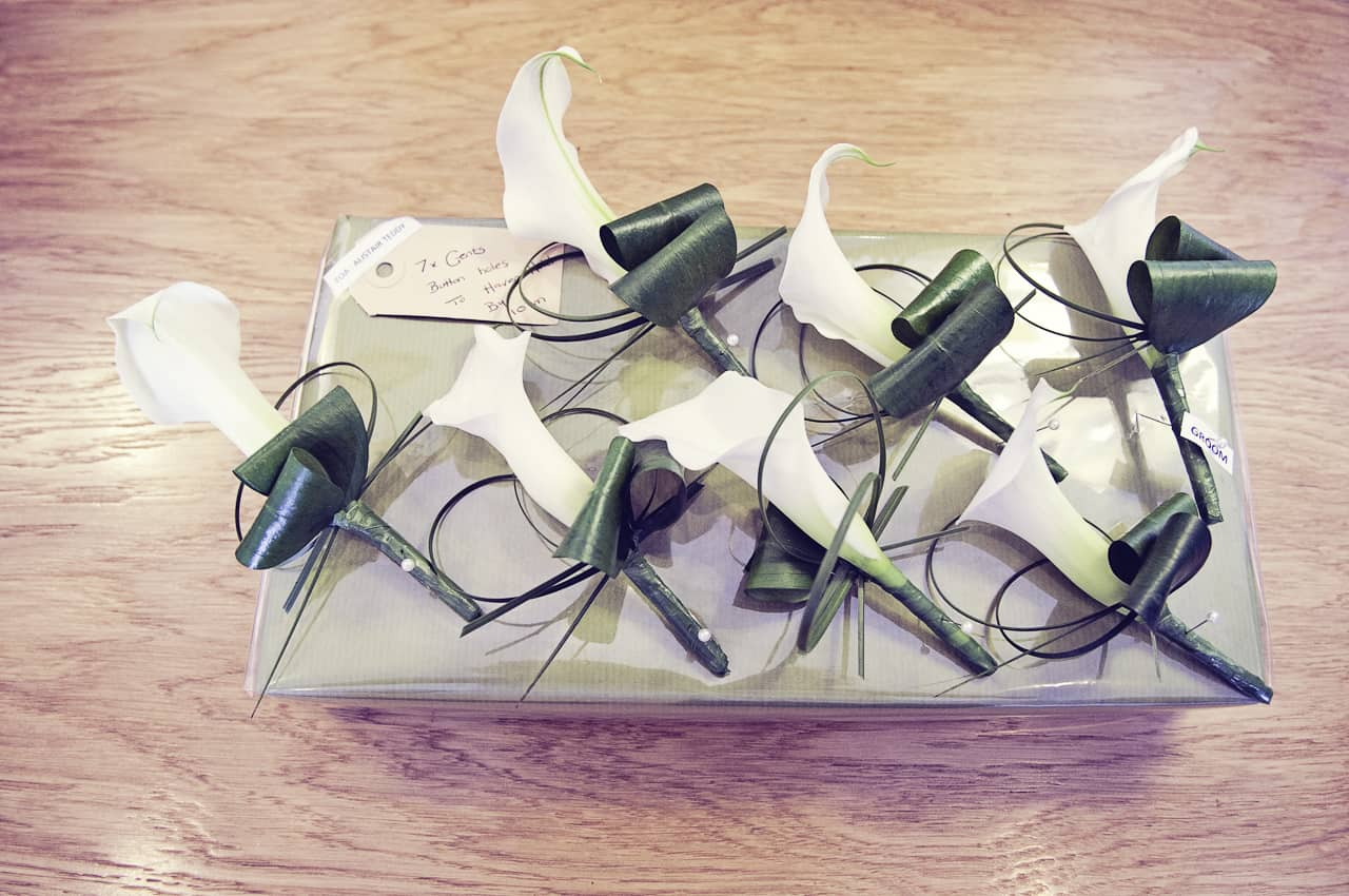 White lilly wedding wedding buttonholes sit on florists box