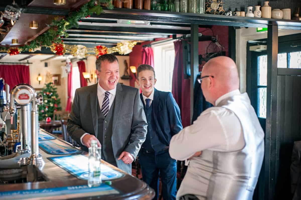 Groom and wedding guests in pub on wedding morning
