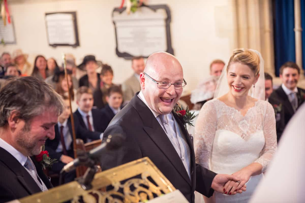 photograph of groom laughing at Hampshire church wedding
