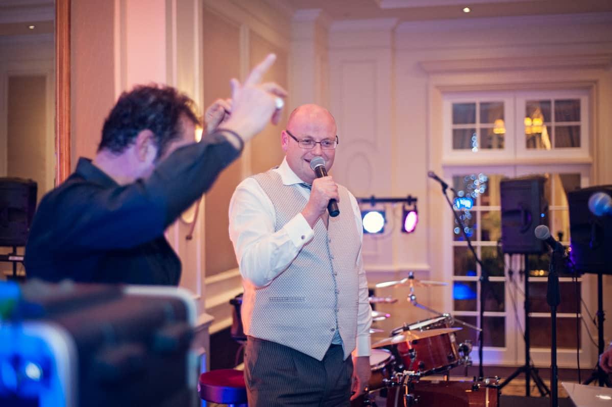 Wedding photography of groom singing with Tom Jones at Hampshire wedding