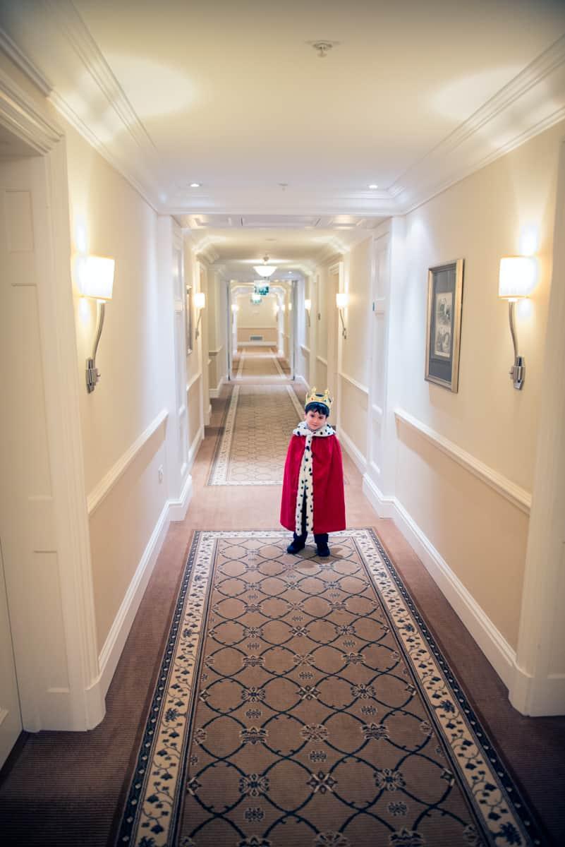 Page boy fancy dress as king in hotel corridor