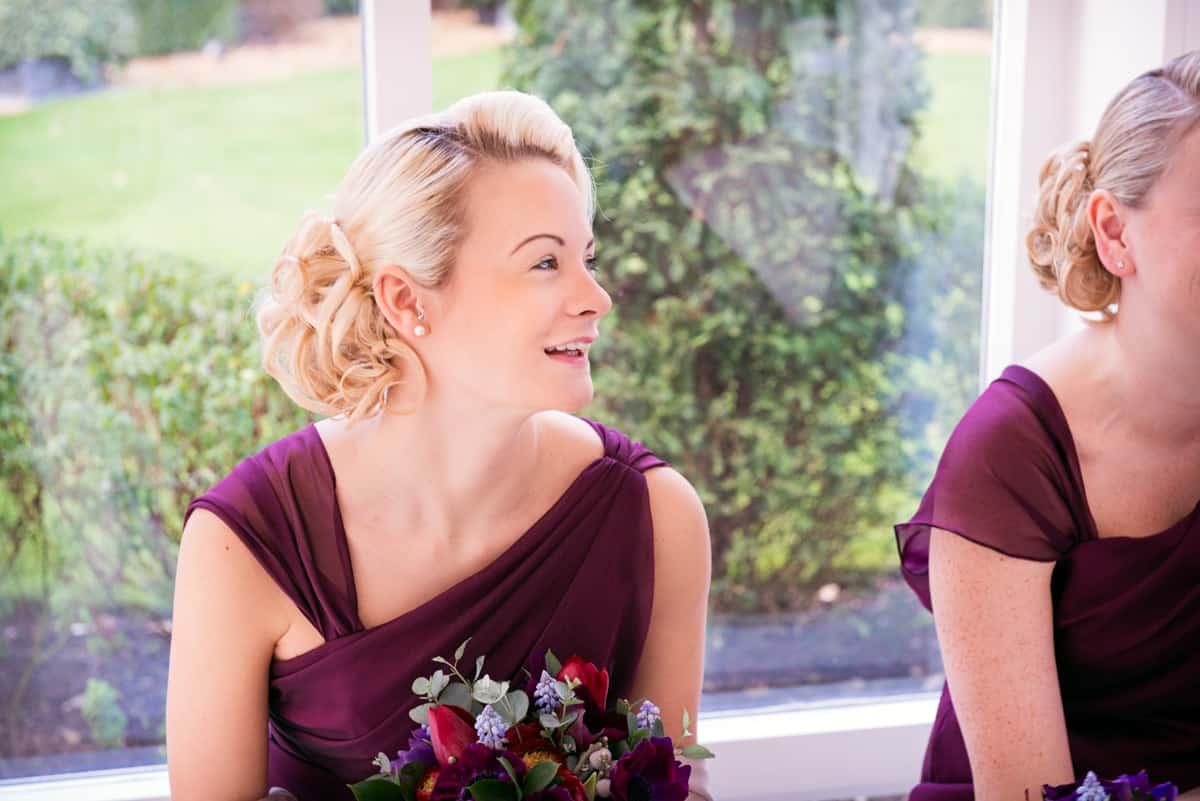 Happy bridesmaid in red bridesmaid dress at winter wedding