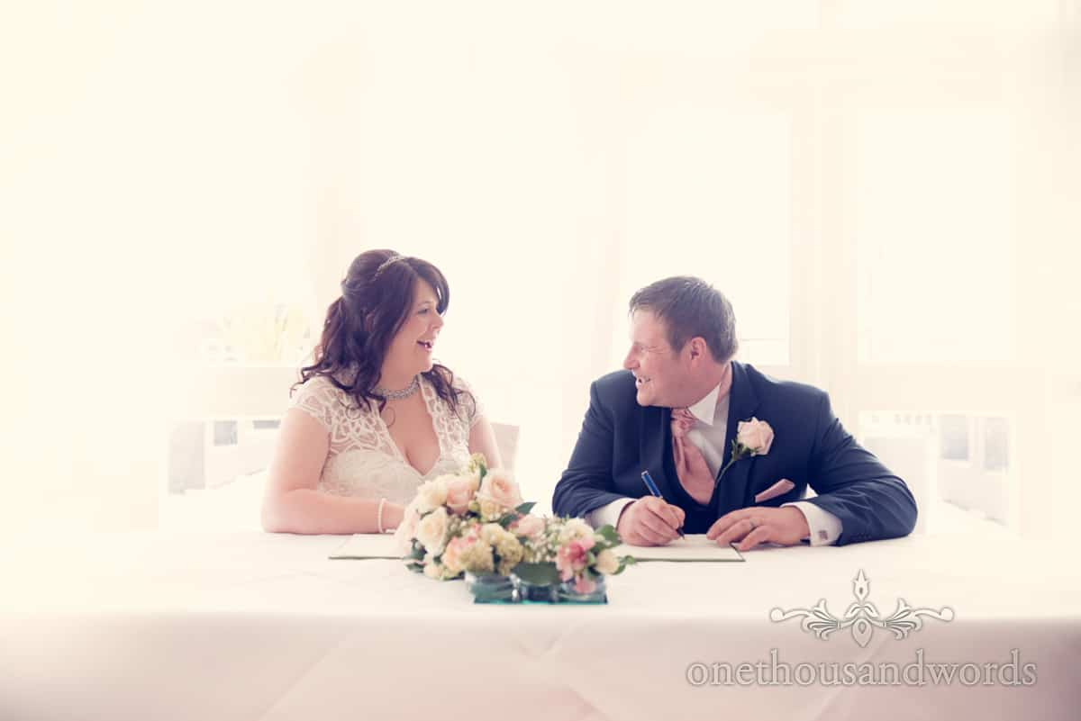 signing the register at Christchurch Harbour Hotel, wedding venue in Dorset
