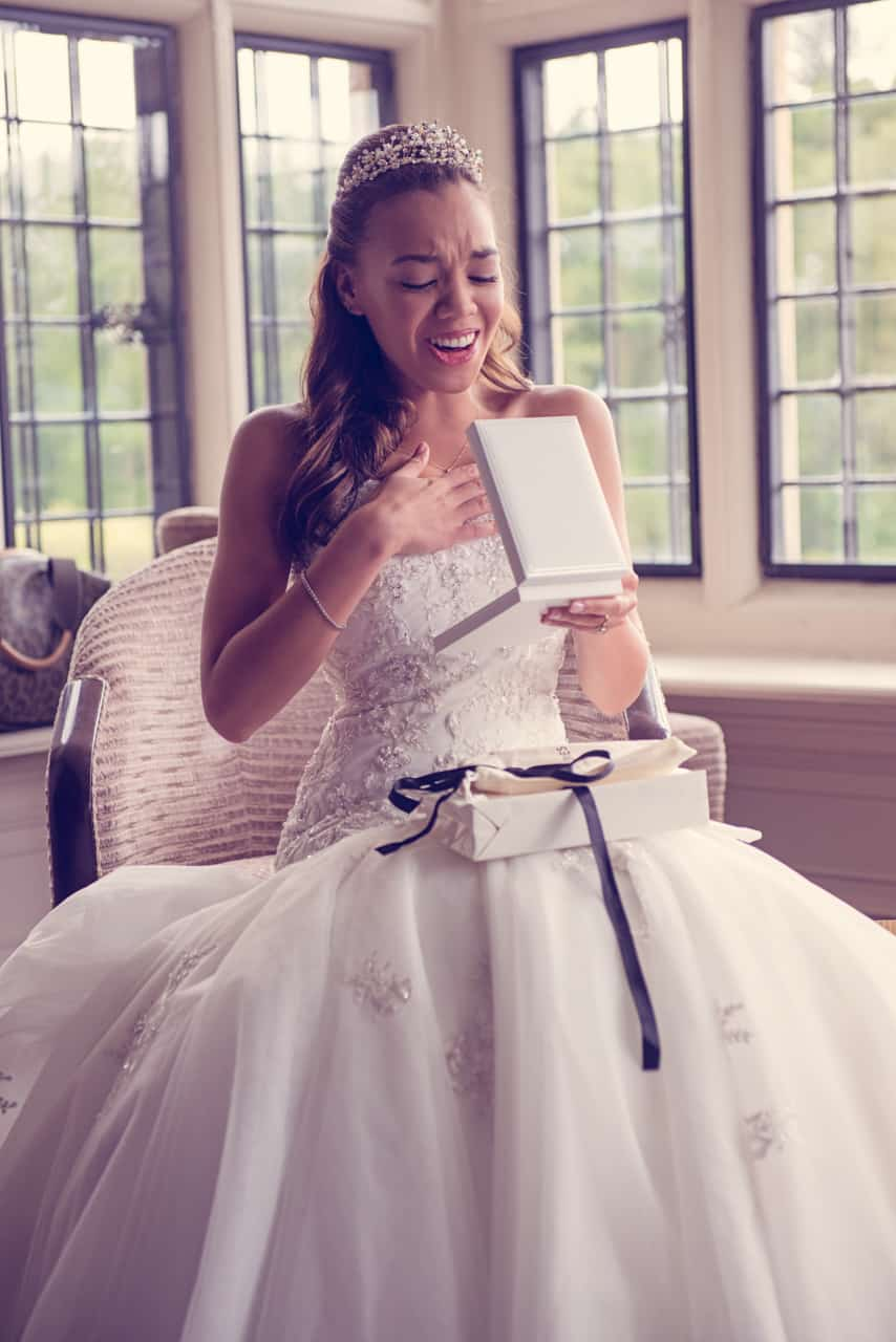 Bride reaction to wedding morning present at Rhinefield House Hotel wedding