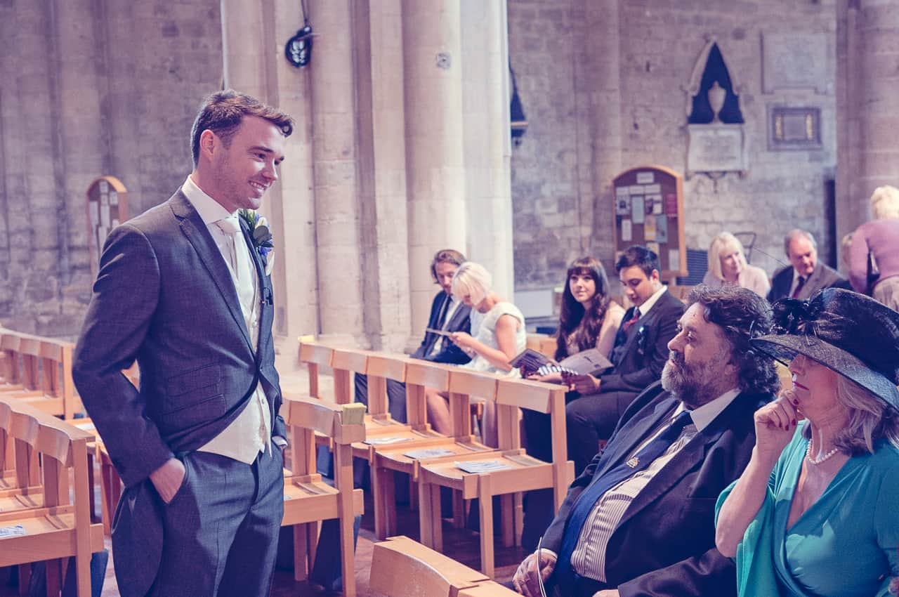 Groom greets guests in Romsey Abbey