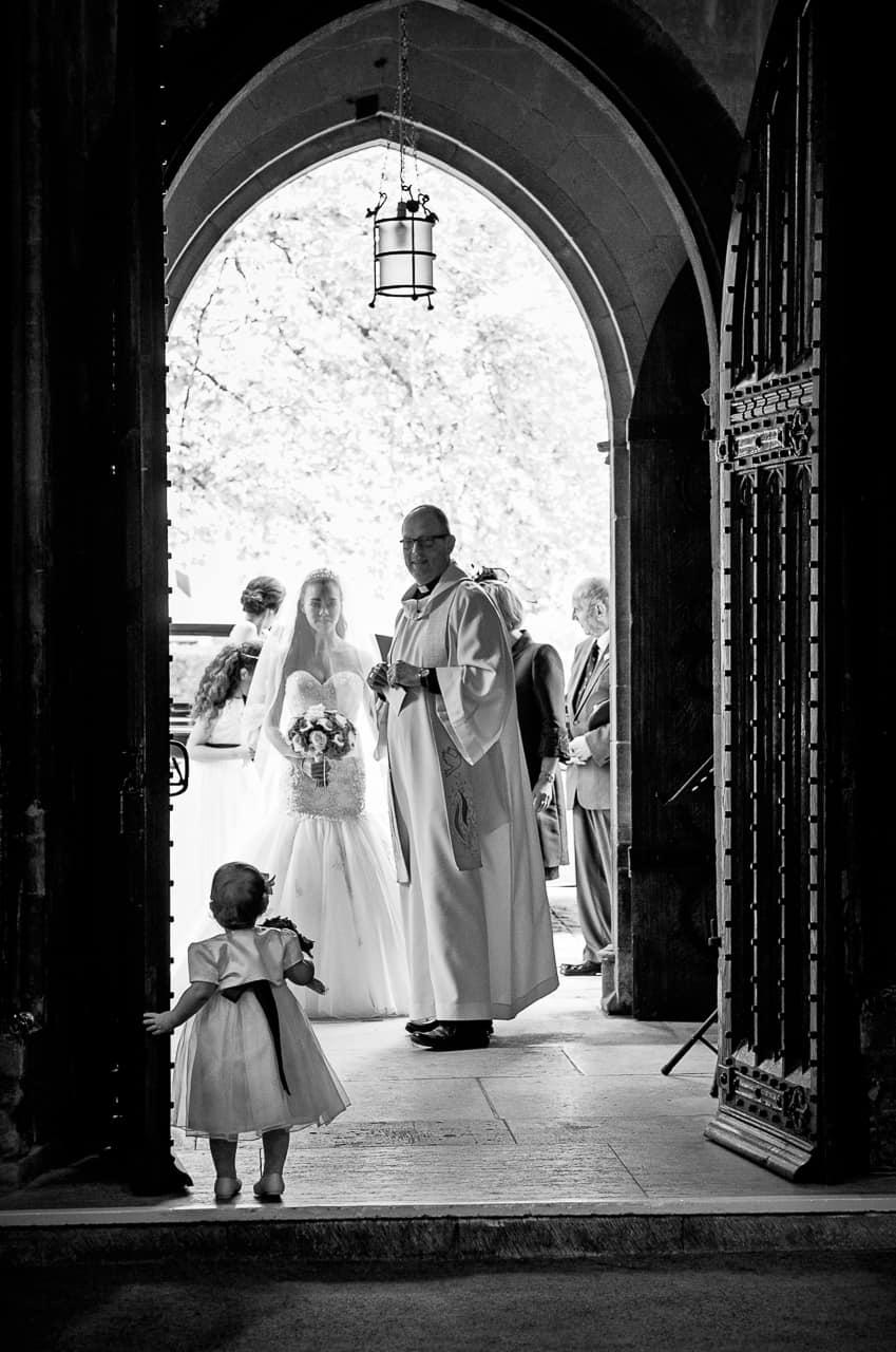 black and white photograph - Bride enters Romsey Abbey wedding venue