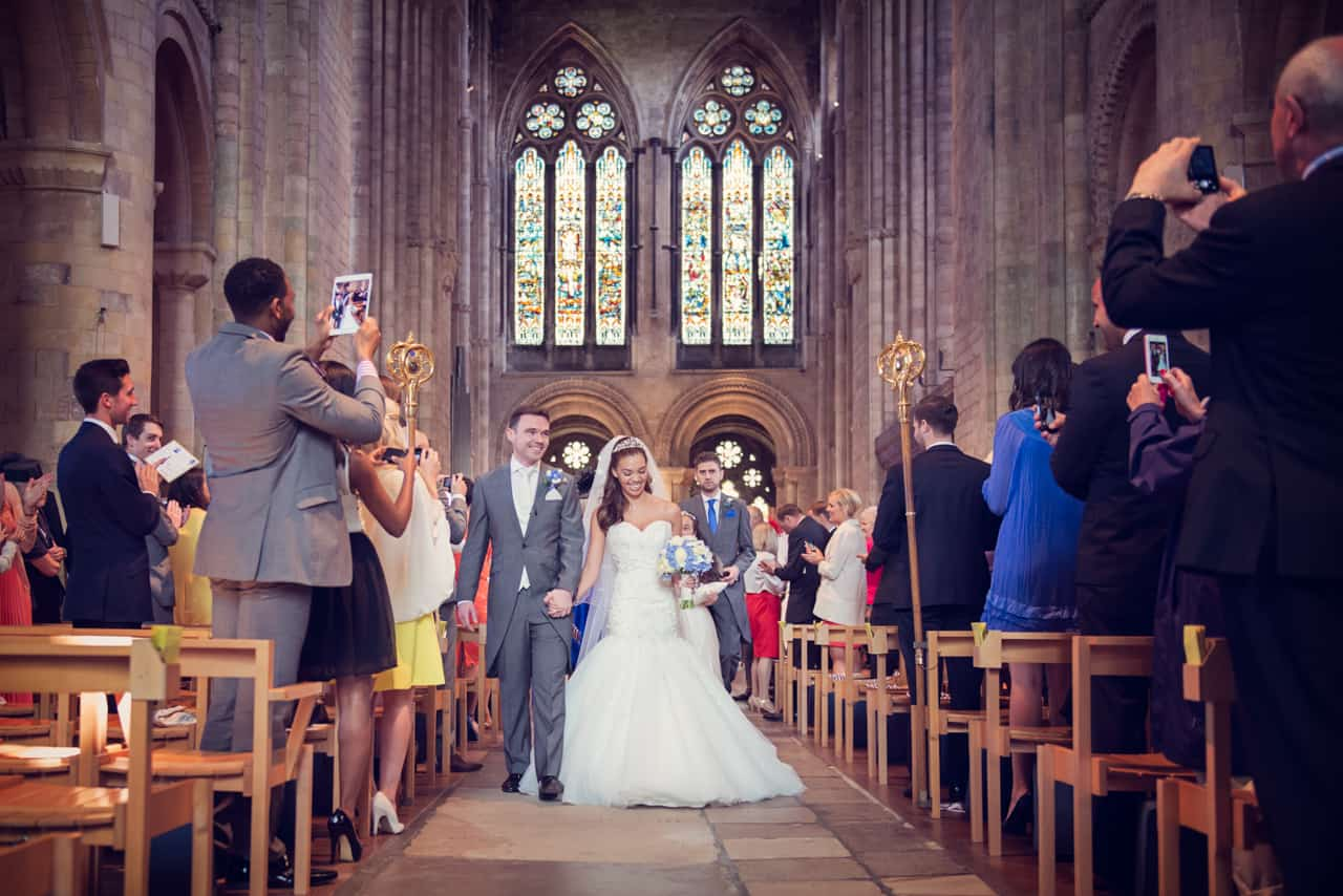 Bride and groom come back down the aisle at Romsey Abbey wedding venue