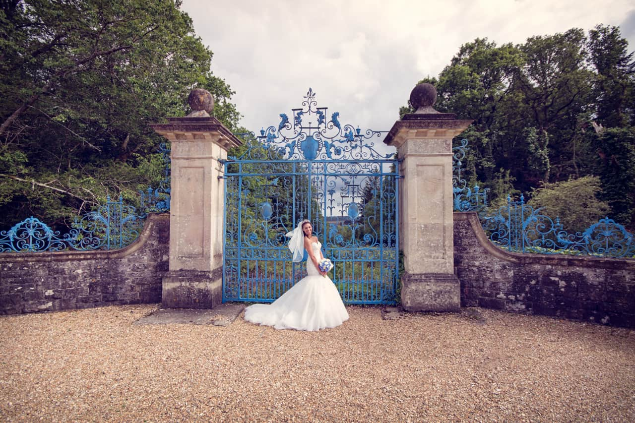 Rhinefield House wedding photographs with bride and blue gate