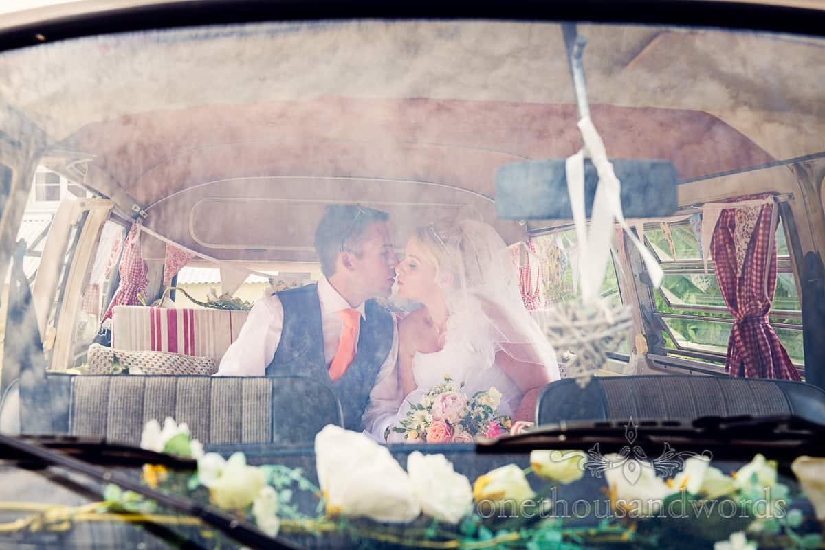 Bride and groom kiss in VW wedding van