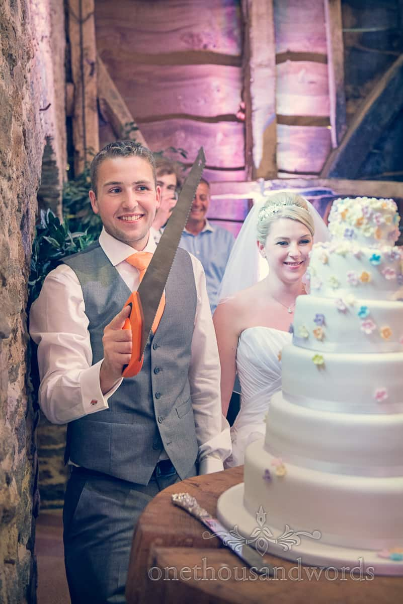 Cutting the cake with a saw wedding photograph