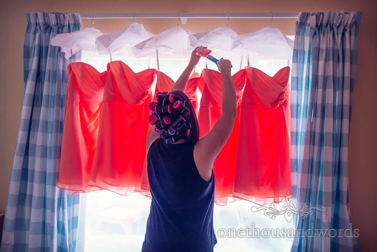 Orange Bridesmaid dresses hang in window