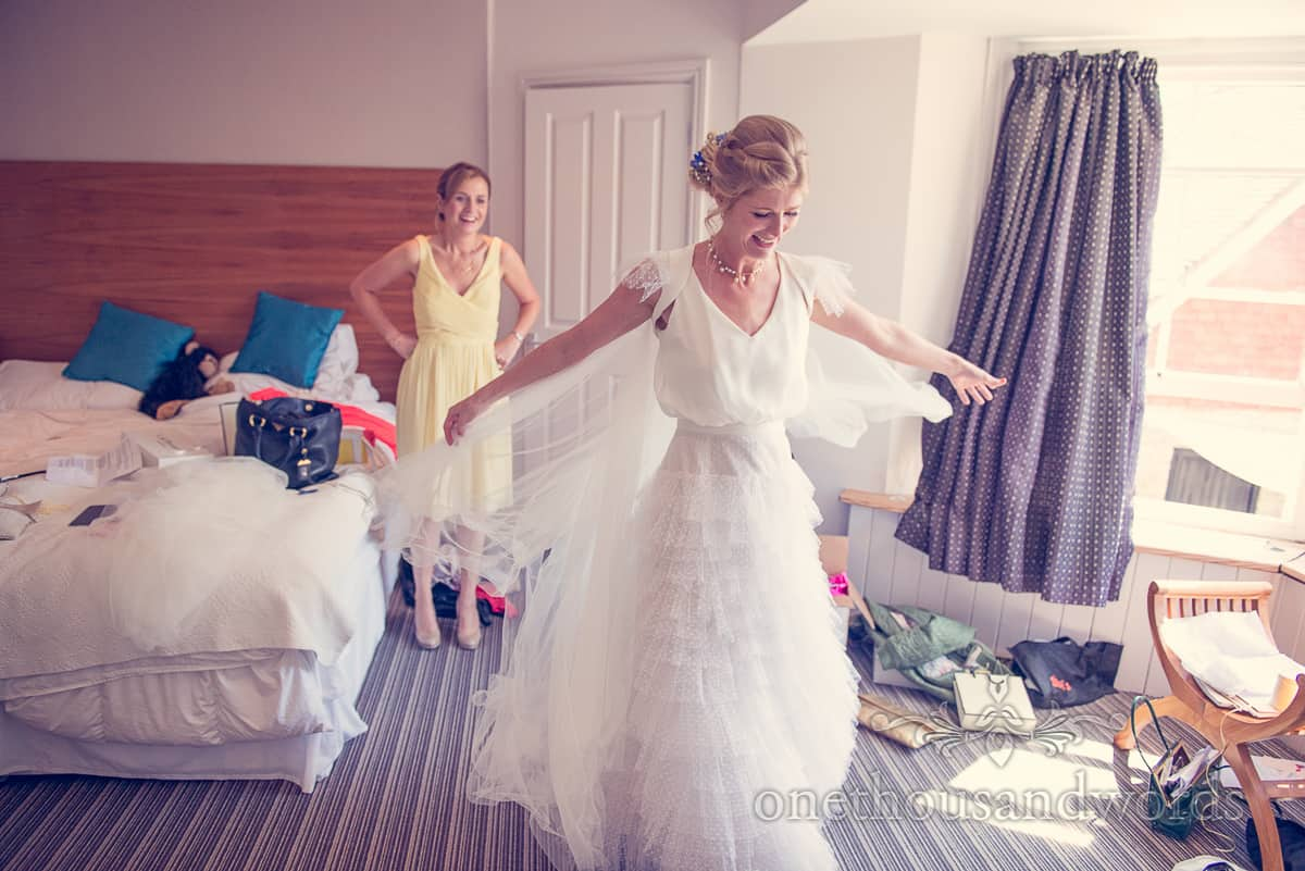 Bride tests out her cape at Lulworth Castle Wedding