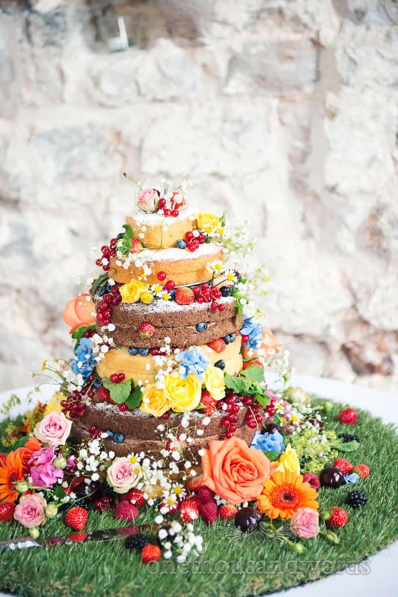 Naked sponge wedding cake decorated with bright coloured flowers