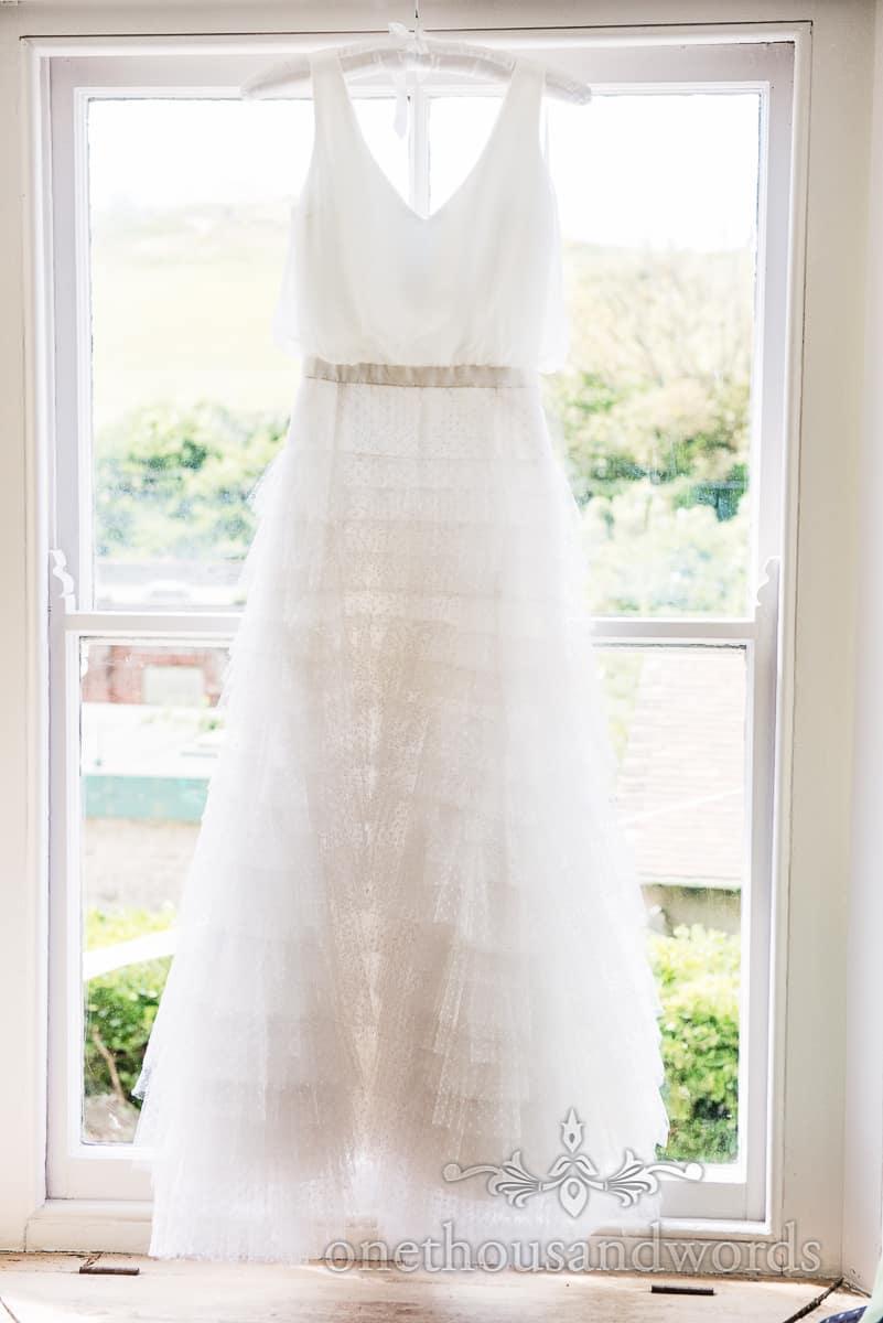 Custom made white wedding dress hangs in window