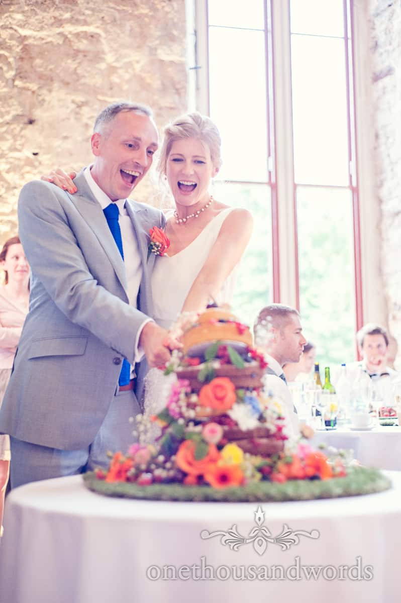 Happy Couple cutting their brightly coloured floral wedding cake