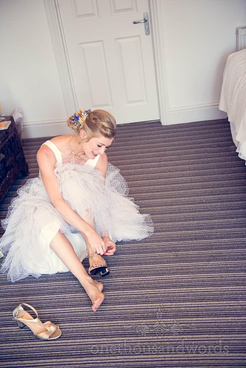 Happy bride puts on her wedding shoes on hotel room floor