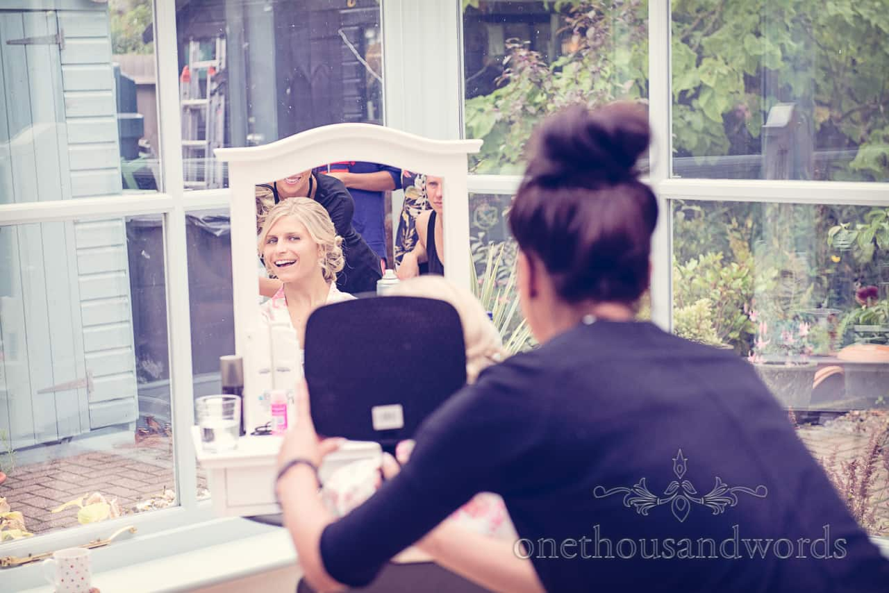 Happy blonde bride looks at wedding makeup in mirror on wedding morning
