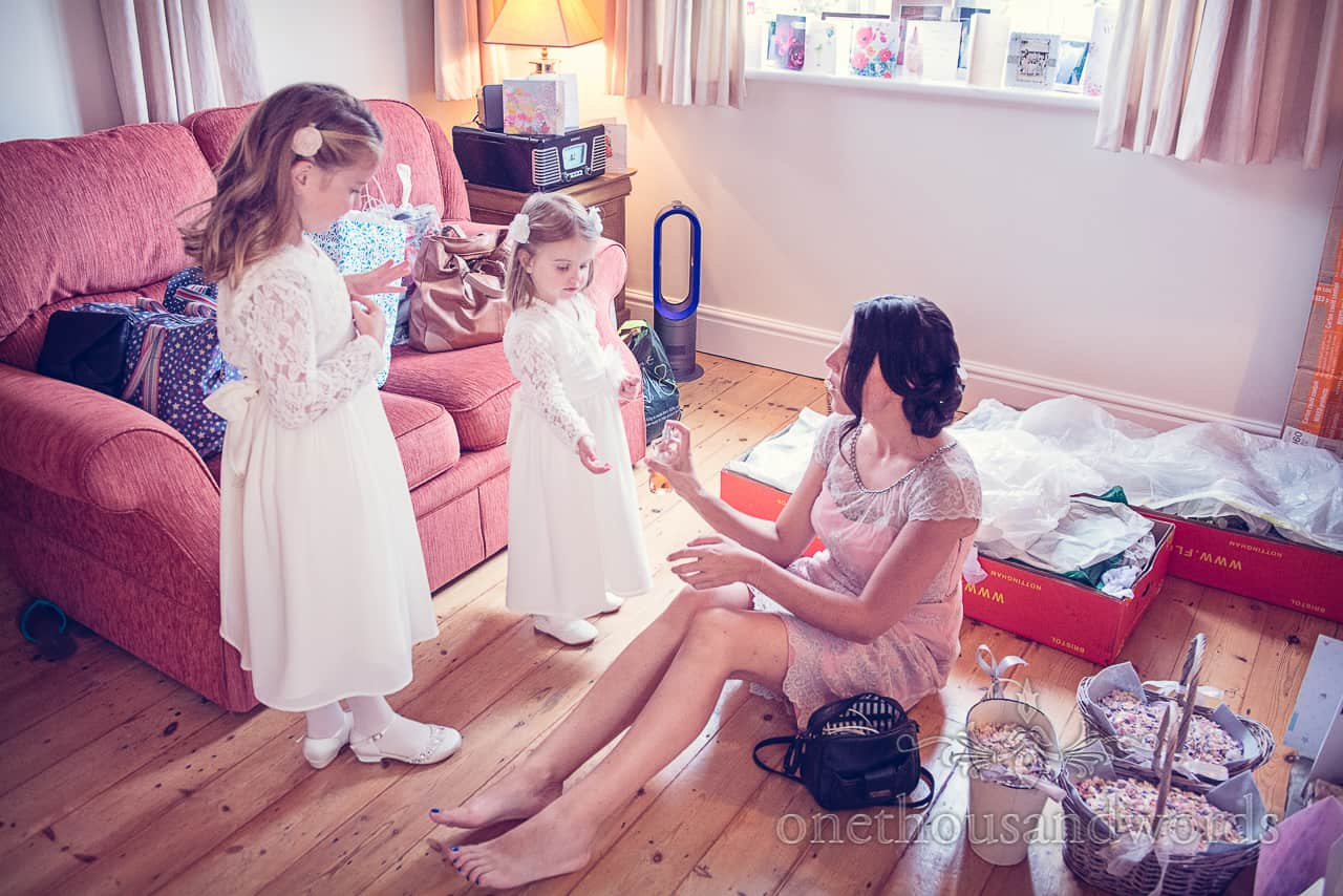 cute flower girls have perfume sprayed by bridesmaid on wedding morning