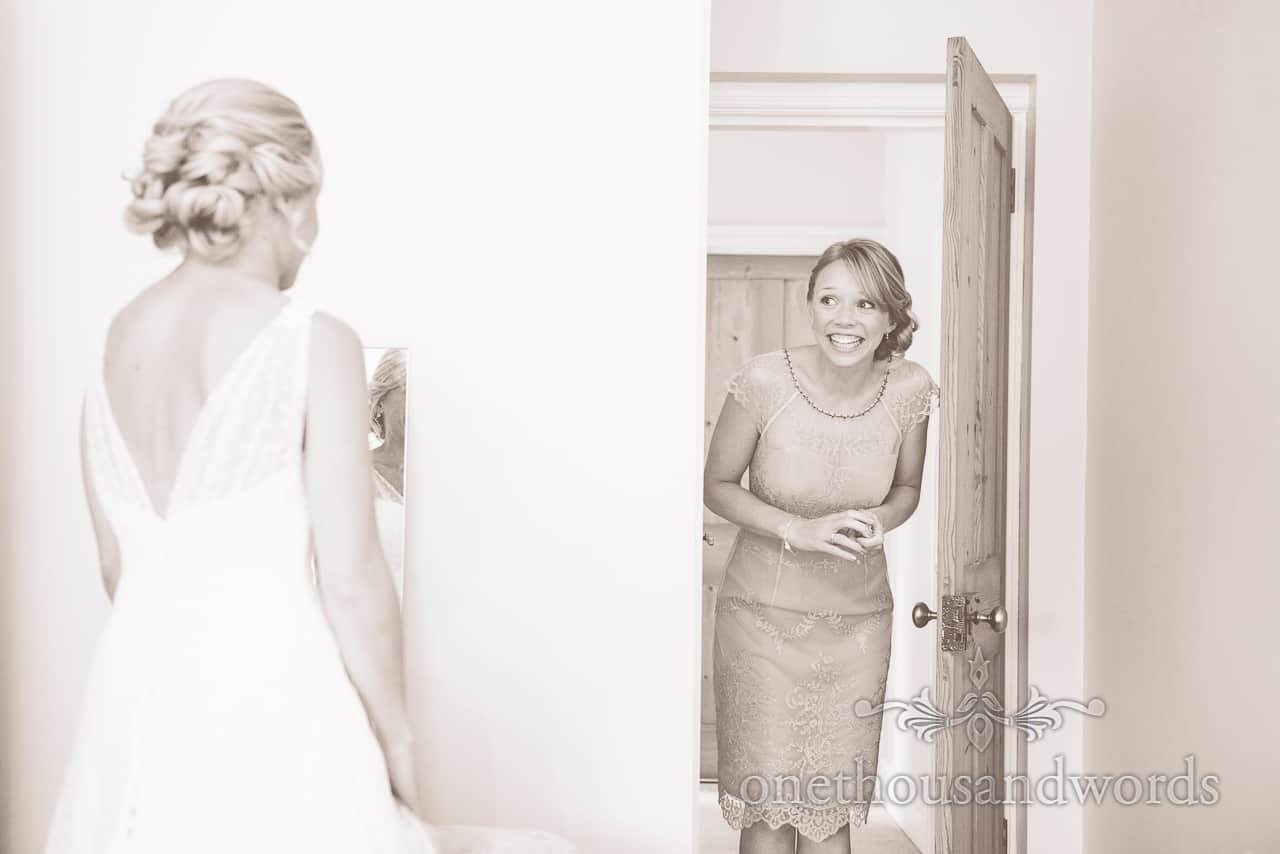 Black adn white photo of bridesmaids first look at wedding dress