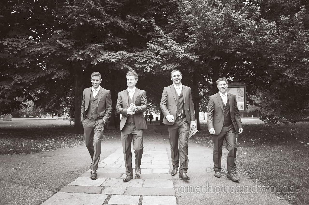 Black and white groomsmen walking to church photograph