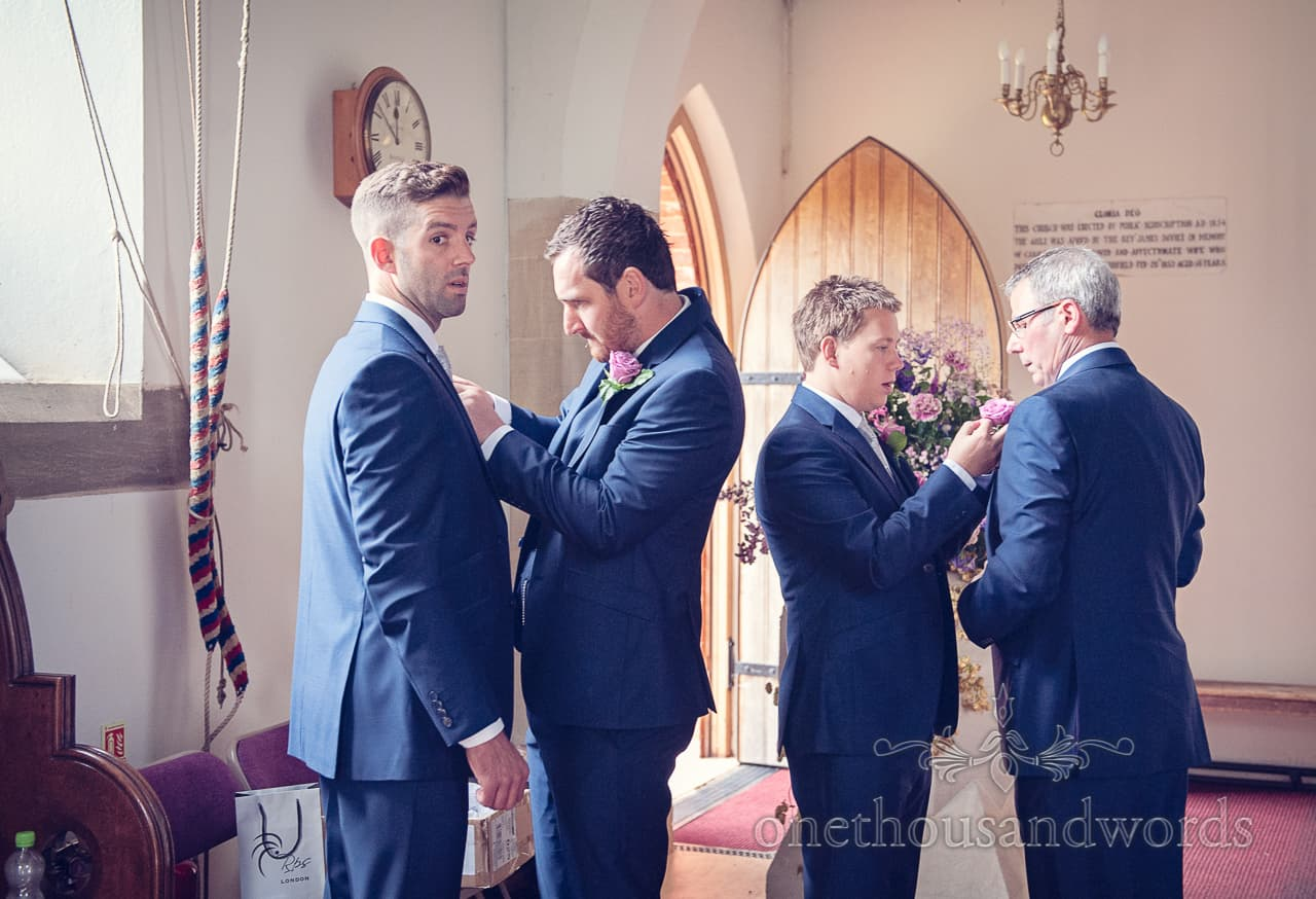 Groomsmen add buttonholes in church before wedding ceremony