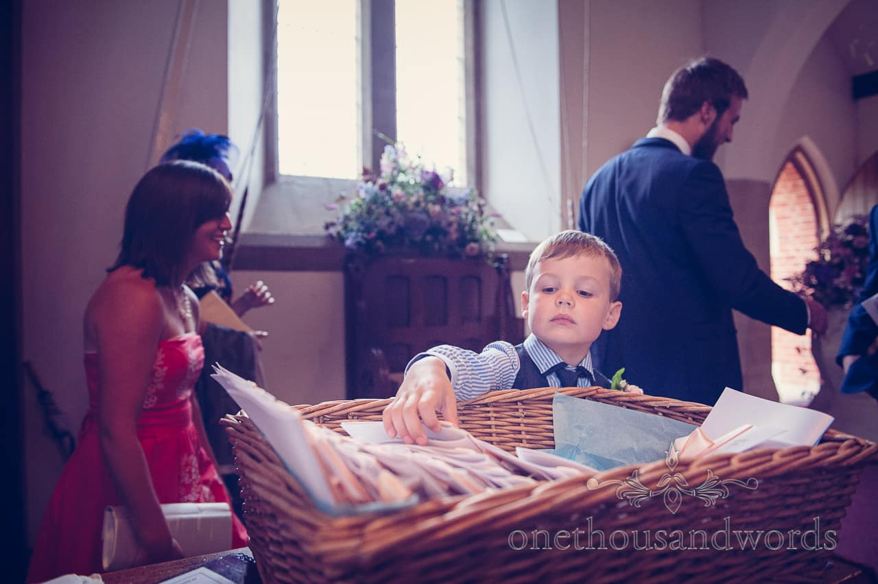 Page boy takes order of service from wicker basket at church wedding