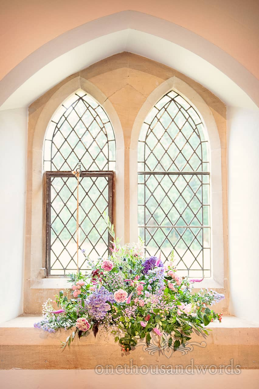 Wedding flowers by Andrew McIndoe in arched church window