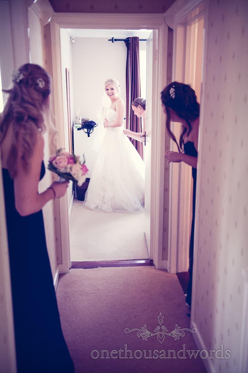 bride puts on wedding dress whilst bridesmaids watch