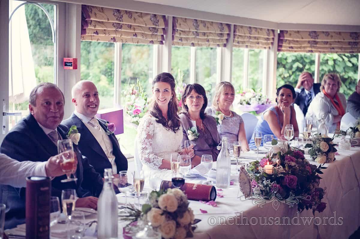 Bride sits at wedding top table at Eastbury Hotel wedding in Dorset