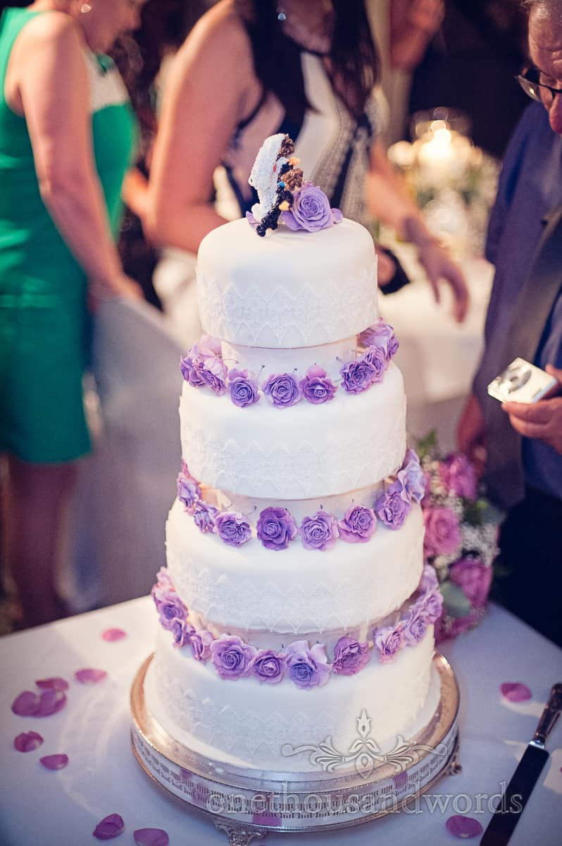 white four tier wedding cake with purple flowers