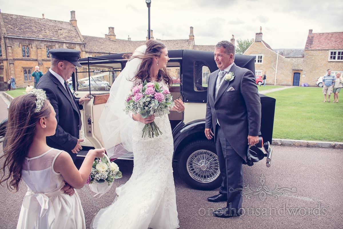 Bride arrives at Sherborne abbey in rolls royce wedding car