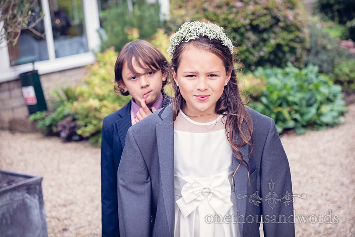 flower girl with floral head band wears suit top at weddign reception