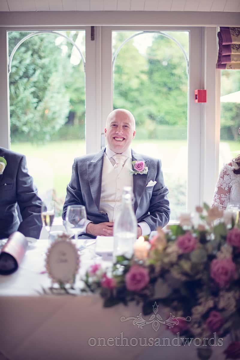Groom laughing at wedding speeches against garden window