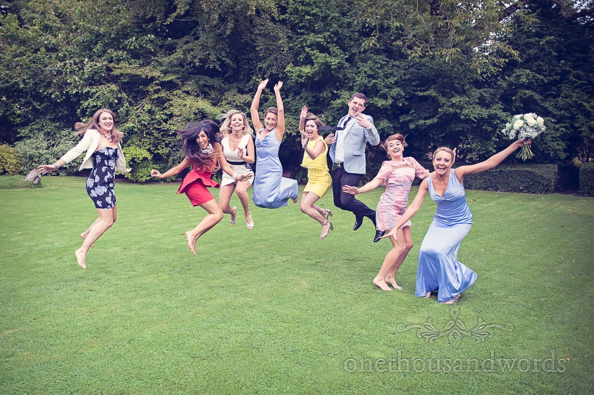 Fun wedding photograph of wedding guests jumping in gardens
