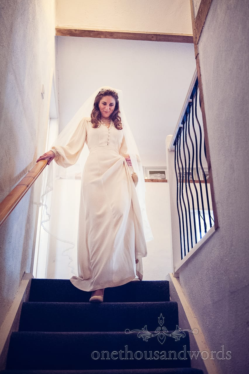 Bride at top of stairs in wedding dress on wedding morning