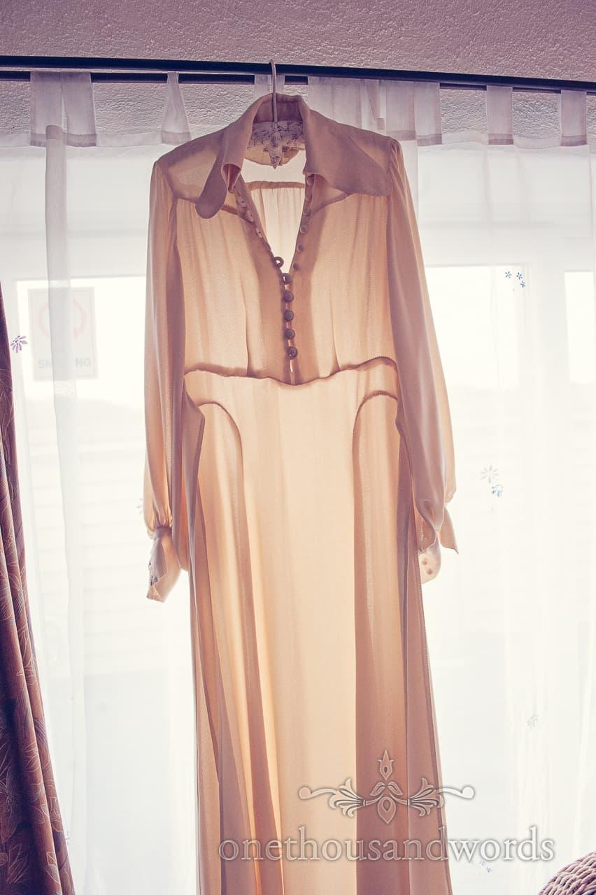 Retro 1970s wedding dress hangs in morning sunshine