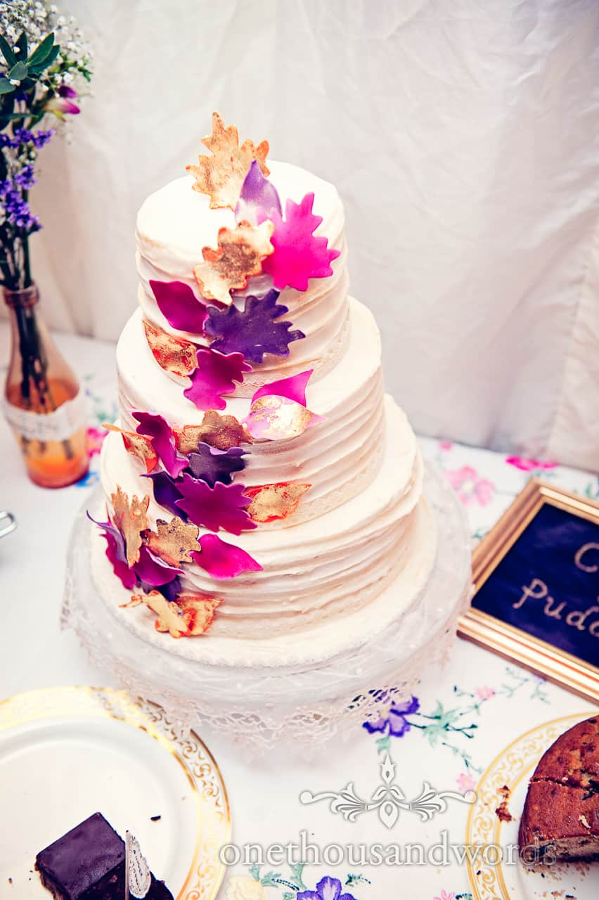 Wedding cake with bright autumn leaves at California farm reception