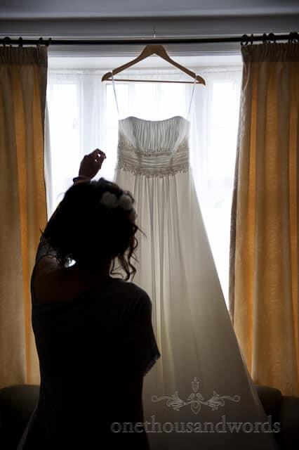 bride reaches for ivory wedding dress wedding photographer wimborne