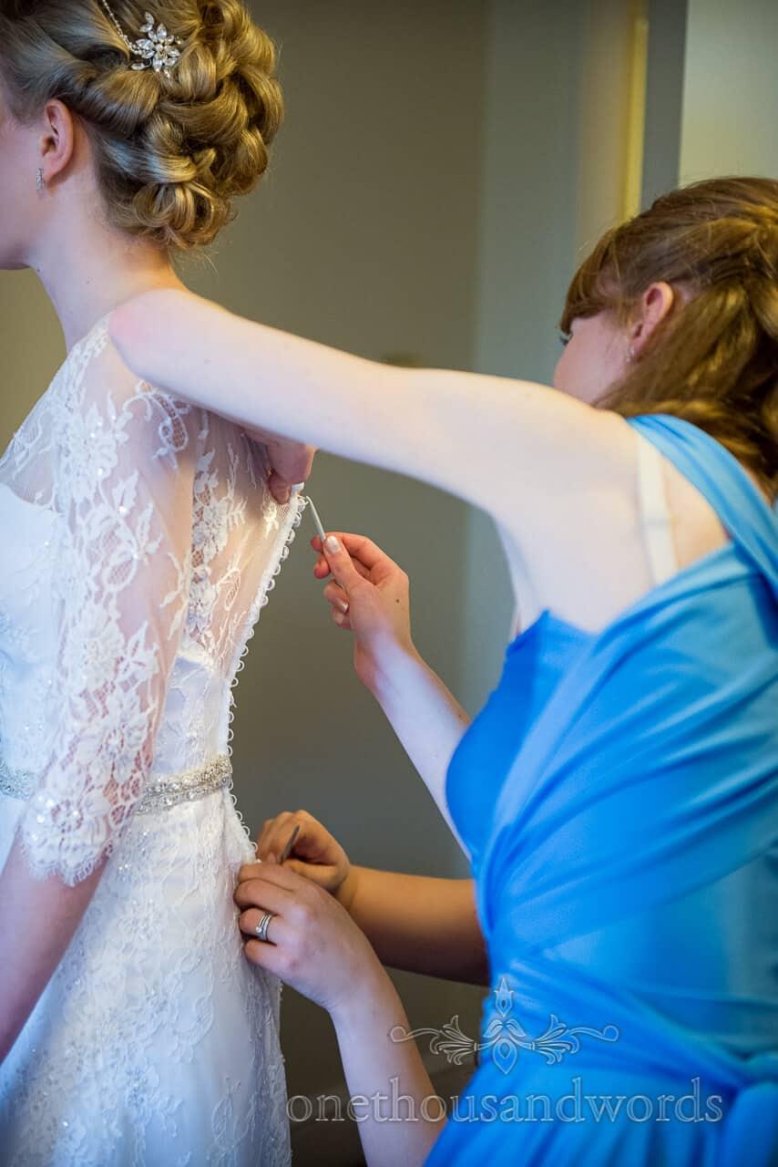 Bridesmaids fasten wedding dress